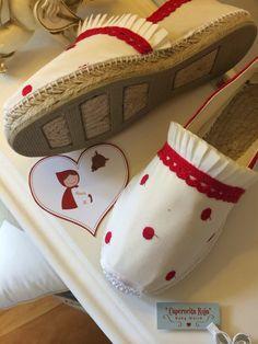 Alpargatas de yute planas clásicas en color crudo. Forradas con tela plumeti, tira plisada vainilla y bolillo rojo. Cosida totalment...