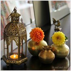 Antique brass kundas with single stems of dahlias tucked into them festival decorations, diwali decorations