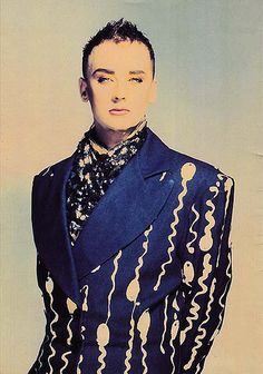 Boy George in a blue blazer with Sperm motif, love his retro look makeup !