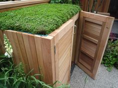 Small timber garden store with a green roof.