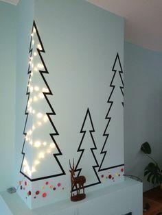 Sapin de Noël mural à fabriquer avec du masking tape noir et une guirlande lumineuse à piles