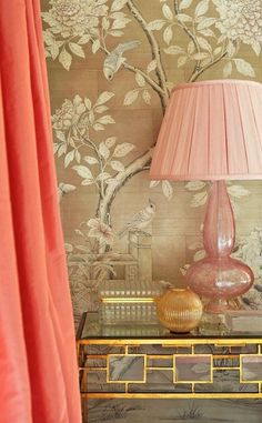 Chinoiserie bedroom with silk salmon pink curtains and taupe chinoiserie wallpaper. Bedroom features gold leaf nightstand with geometric pattern filled with pink glass lamp with pink pleated shade and decorative bowl and box.