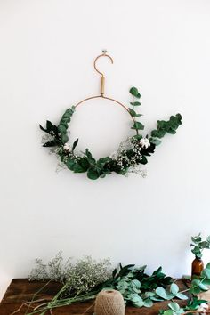 Continue the minimalistic theme of your decor with a wreath that has just enough foliage. Freckle And Wulff created this wreath with a metal hanging ring, twine and an assortment of greenery and flowers such as eucalyptus, holly leaves, ivy and baby's breath.