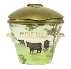 A Staffordshire 'Pure Milk Pail', 19th century, with a hinged brass cover above the tapering band moulded body with printed and hand painted decoration of Lombard cows in naturalistic landscape, printed in gilt 'Pure Milk' with applied swag handles, printed mark 'The Dairy Supply Co. Ltd, Museum Street, London, WC', inscribed D49E 38cm diameter £1000-1500 9th September 2014