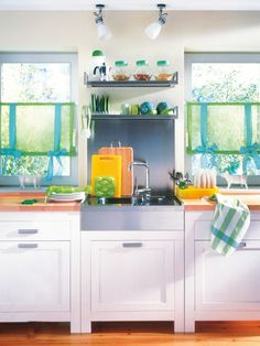 Aprovecha los huecos  En esta cocina se ha sacado utilidad a la pared que había entre ambas ventanas. ¿Cómo? Con un frente de aluminio que la protege de las salpicaduras del fregadero, además de un estante y una balda con escurreplatos.