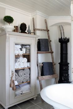 It is perfect to store towels in an antique cabinet. The old ladder is used as a towel hanger.