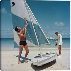 American actor Hugh O'Brian (left) hoists the sail on a dinghy, Antigua, West Indies, 1961. (Photo by Slim Aarons/Hulton Archive/Getty Images)