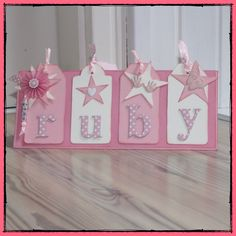 handmade baby card: *PeiSign* .... monochromatic pink ... short and wide format ... four decorated tags ... monochromatic pinks ... name spelled out in large die cut numbers from polka do papers ... luv it!