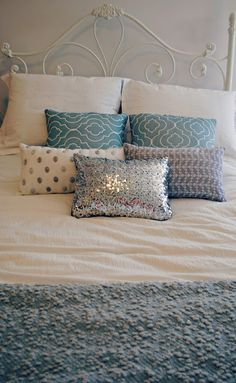 Plain white bed with accent pillows and blanket