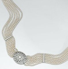 DIAMOND AND SEED PEARL CHOKER-NECKLACE The center decorated with an oval medallion of key-fret design joined to six strands of seed pearls with diamond-set spacer bars and clasp, the whole set with 157 round diamonds weighing a total of approximately 3.25 carats, mounted in platinum