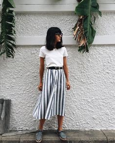 White short-sleeved t-shirt with white and gray vertical stripe button-up midi skirt. Side pockets. Skirt belted with black leather belt. Huarache-style lace up shoes. Exotic in spite of herself. Style Planet #tropical outfits #summer outfits women #summer skirt outfits