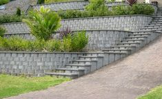 Multi-tiered brick retaining walls showcases a stunning design and matching staircase on the side. Its unified gray color makes the green plants stand out. Retaining Wall Bricks, Backyard Retaining Walls, Gabion Wall, Sloped Backyard, Sloped Garden, Terraced Landscaping, Front Yard Landscaping, Landscaping Ideas, Stone Landscaping