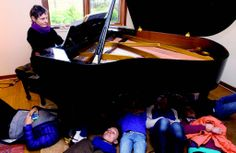 Students from the Taos Waldorf School's,sixth-grade class rest beneath Annata Black's August Forester piano in her home Monday (April 28). As she plays, the students can feel how their bodies resonate with with music. Photo by Elliott Martin