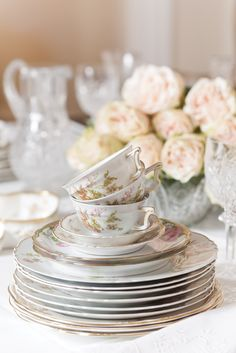 Honeyed, delicate edges of a floral china pattern and a centerpiece of fresh-cut blooms add charm to this beautiful Beaux-Arts-style interior.
