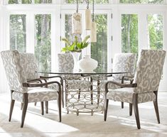 The textural fretwork adorning this table base is a bedazzling embellishment for a sleek, contemporary dining room. The table base is finished in hand-burnished silver leaf and paired with a tempered glass top. Soften the look with upholstered dining chairs in your choice of hundreds of custom fabrics.