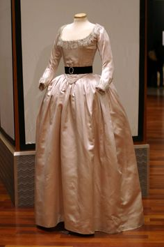 A gown of pale pink silk worn by Kirsten Dunst in her portryal of Marie-Antoinette. Accented by a black velvet sash with a gem-studded brooch, as well as a lace collar and sleeve cuffs.