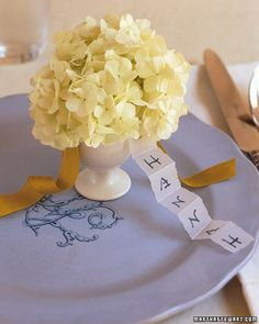 Egg cup place-card holders  really cute idea, simple, to the point, and flowers [or candy whatever you put in it] for everyone!