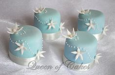 Cornflower blue miniature cakes with white flower detail. By Queen of Cakes