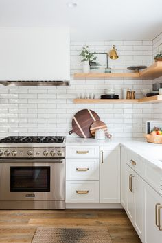 White kitchen cabinets, white subway tile, and light wood open shelving really make this beautiful, neutral kitchen. White Kitchen Cabinets, Kitchen Tiles, Kitchen Countertops, Kitchen Decor, Kitchen Wood, Kitchen White, Floors Kitchen, Kitchen Shelves, Kitchen With Subway Tile