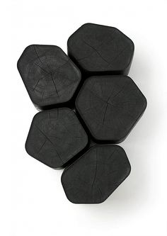 Black wooden table emulating volcanic basalt. — Designspiration