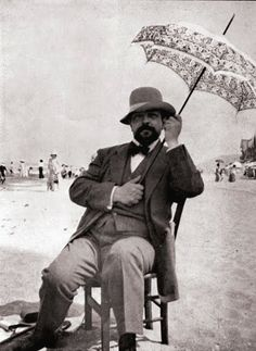 Claude Debussy holding an umbrella on a beach.