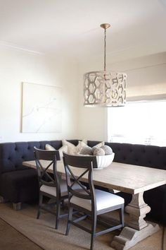 Chic breakfast nook features a L shaped black tufted banquette facing a reclaimed wood trestle ...
