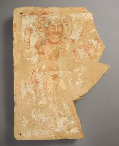 The god Shiva/Oesho is depicted on a votive panel; four-armed and three-headed, with a prominent third eye, he wears an animal skin and a belted, diaphanous garment and holds a trident. Bactria C. Asia. Kushan