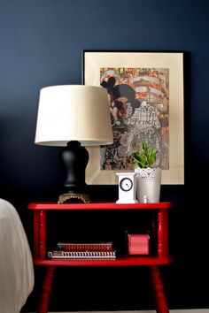 Dark Navy walls with that high-gloss red nightstand - rich, classy, cozy...