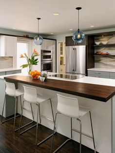 HGTV presents a contemporary blue kitchen with open floor plan, orb pendant lights, and a large island with Wenge wood countertop.
