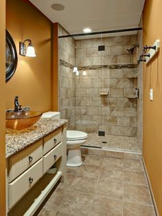 pumpkin/camel bathroom w/ amber sink bowl, light neutral floors and shower, white counter and bronze fixtures