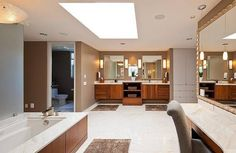This Seattle bathroom has white tile flooring, a marble counter, large rectangular bathtub, wood cabinetry, dual vanities, and skylight.