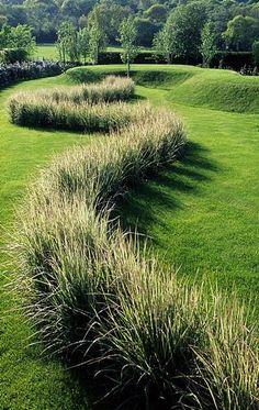 A line of ornamental grass Calamagrostis 'Overdam' Turf earthworks ...