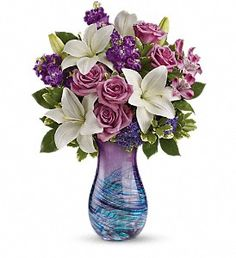 Lavender roses, white asiatic lilies, purple alstroemeria, purple stock and purple seafoam statice are arranged with variegated pittosporum and lemon leaf