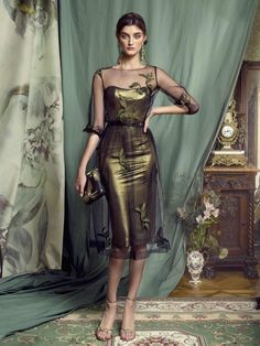 Style #443 is a truly chic gown, it features a shimmering green fitted gown beneath a black, sheer a-line gown, complete with leaf embroidery in a matching green fabric.