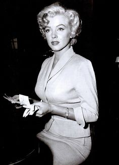 Marilyn holding fake pornographic letters and snapshots of a Monroe lookalike appears in a California courtroom in 1952 to put a stop to the mail order business being promoted at her professional expense.