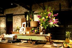 Vintage Cart used on Farm Buffet Table with old crates and flowers to create a centerpiece. www.shabbyandchicrentals.com