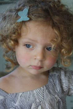 A curly haired cutie wearing hello shiso's butterfly clip.