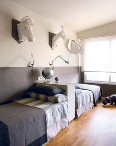 Raumtrenner für ein geteiltes Kinderzimmer: Zwei Betten an der Wand und dazwischen ein Regal.