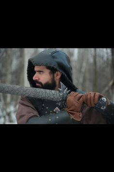 Man in leather armor weilding an evil sword in the forest.  Calimacil LARP Sword : Moloch III, Stone of the Abyss