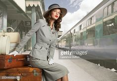 Woman in 1940's style clothing, sitting on luggage at train platform