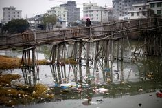 A woman walks on a bridge over a polluted river at a suburban area of Wenzhou in Zhejiang province