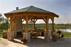 Structural log gazebo creates an inviting outdoor space.  Masonry fireplace, grill and refrigerator provide the comforts of home outside.