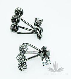 Kolczyki srebrne, rodowane i oksydowane, wysadzane cyrkoniami o szlifie brylantowym z ozdobnym zapięciem.