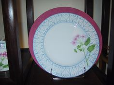 dinner plate hand painted Limoges porcelain, with pink charger. pelargonium (geranium) flower, and sky bue garden border