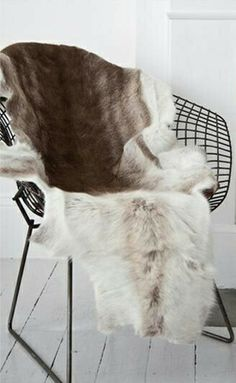 The soft natural animal skin contrast against the black, geometric, metal chair.