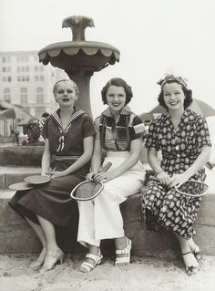 1930's women sitting on a fountain.