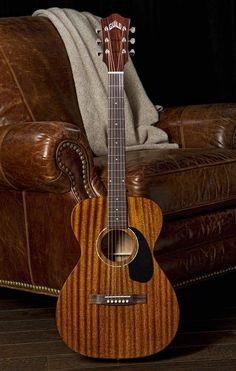 Acoustic beauty - Guild GAD Series M-120 Guitar made by Taylor with dark stripes in wood grain is another of my MOST POPULAR RE-PINs. No cutaway, small dark pickguard to show more of the body. RESEARCH #DdO:) - http://www.pinterest.com/DianaDeeOsborne/instruments-for-joy/ - INSTRUMENTS FOR JOY. Also a dreadnought version D-125. Lovely photography setting w deep red brown leather easy chair, & a cloth that lets guitar neck and headstock stand out despite dark background. Pinned via Brandy…