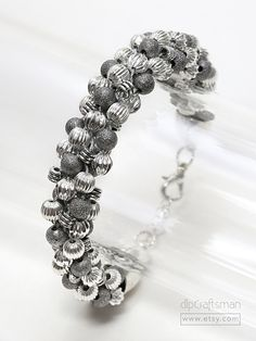 FREE SHIPPING within the USA! Chunky Silver Ball Bracelet. A gleaming mix of silver shapes and finishes! This chunky beaded Kumihimo bracelet combines corrugated, ribbed and stardust beads in gleaming silver plate, antique and sparkle finishes. Large bullet-shaped end caps, chain extender and lobster claw clasp finish the braid. All in silver plate. This eye-catching bracelet is perfect for Winter Holidays! Kumihimo is an ancient Japanese braiding art, combining silk strands or other...