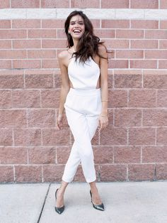 Sara Sampaio wears a white jumpsuit with leather heels
