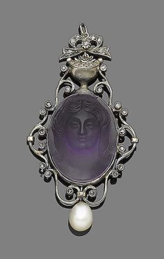 A carved amethyst and natural pearl pendant  The oval amethyst carved to depict a female bust, within a scrolling openwork surround highlighted with rose and single-cut diamonds, suspending an 8.0mm natural pearl drop, length 4.8cm, fitted case